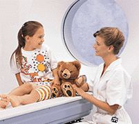 A technologist sits with a child before a CT scan